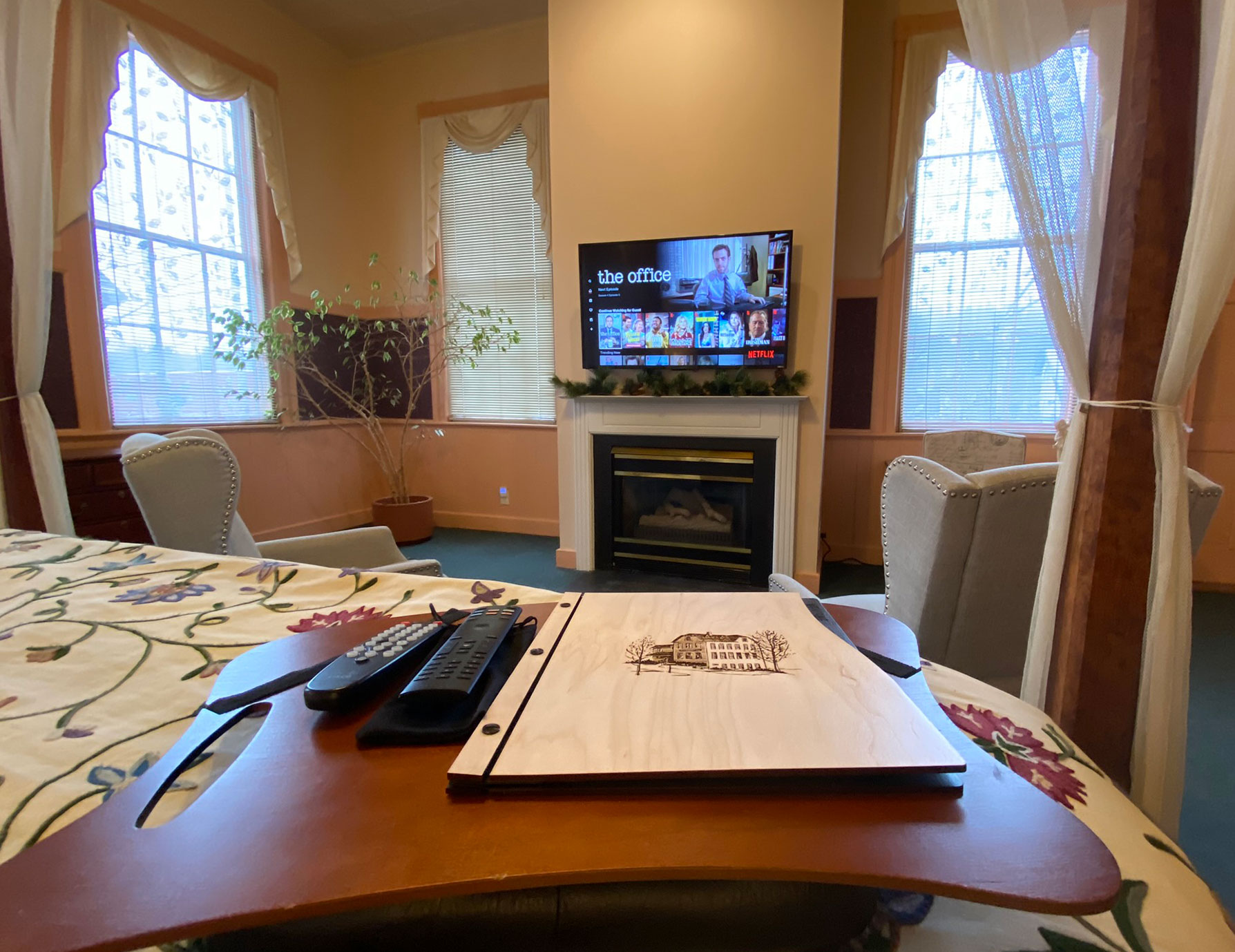 Remotes and guide book on lap desk on bed - Berkshires Lodging