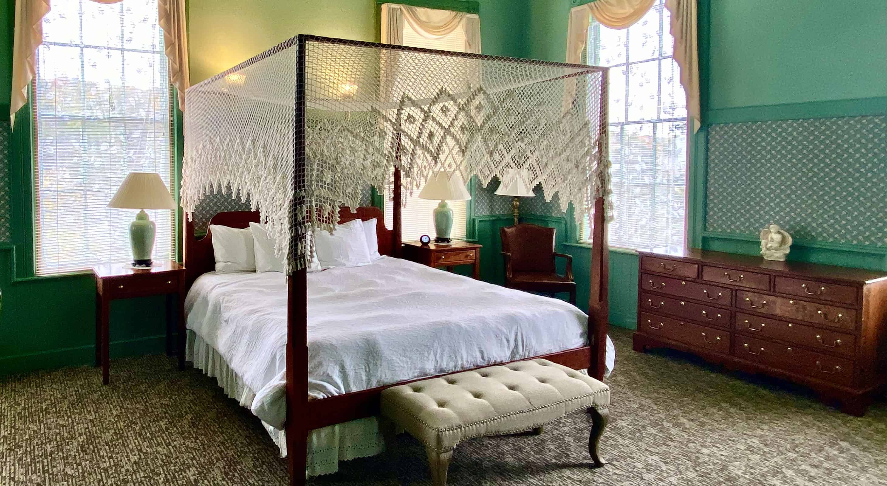 four poster bed with lace and green walls