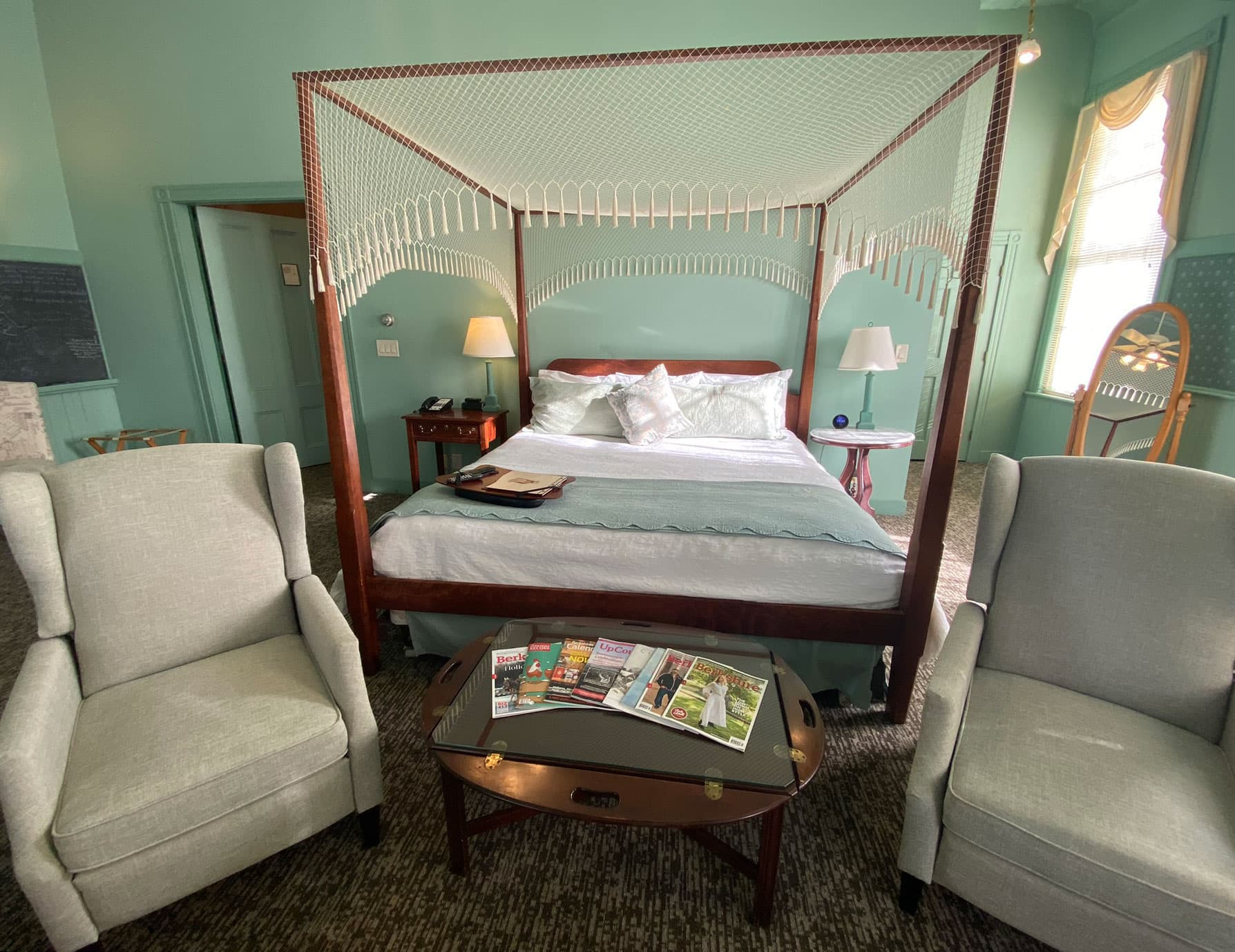 View of magazines and sitting area at the foot of ornate bed - Lenox Inn