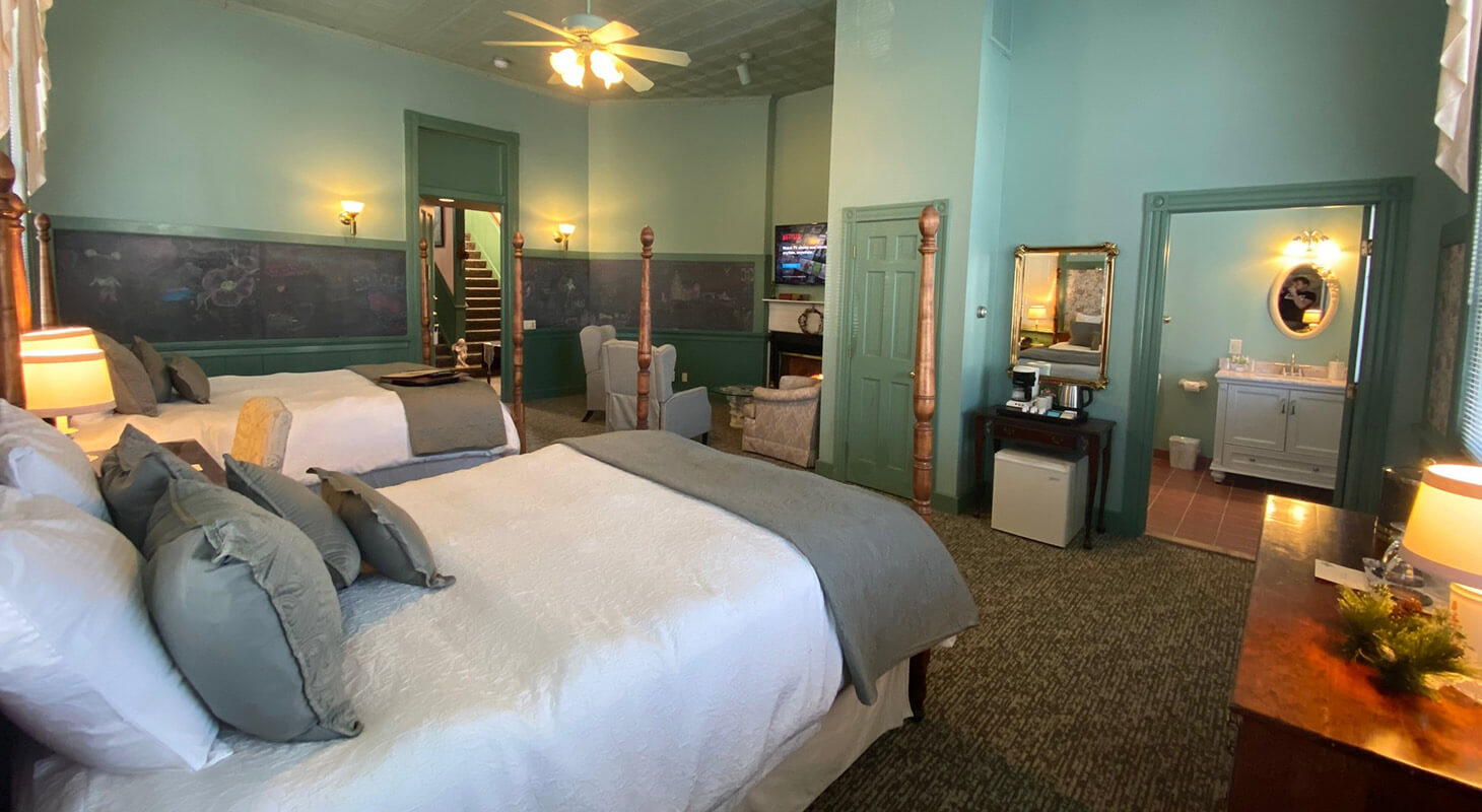 La Sedgwick room with beds, bathroom, and sitting area with TV
