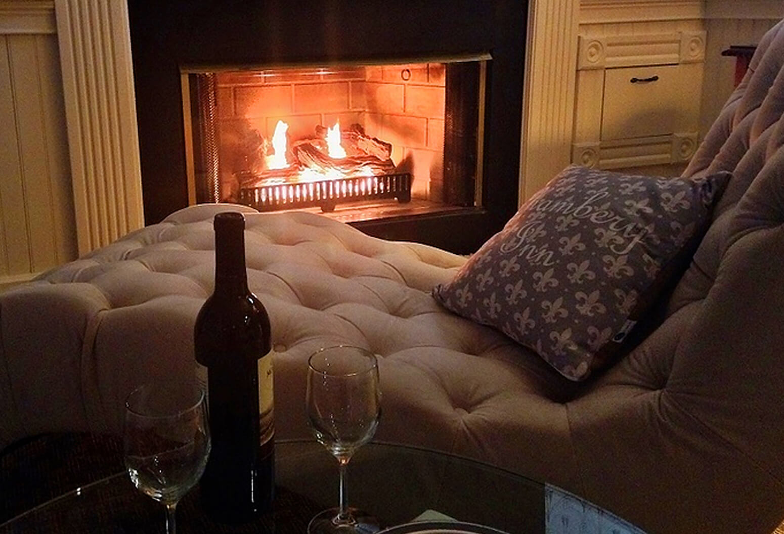 cozy fireplace and wine by a chaise lounge